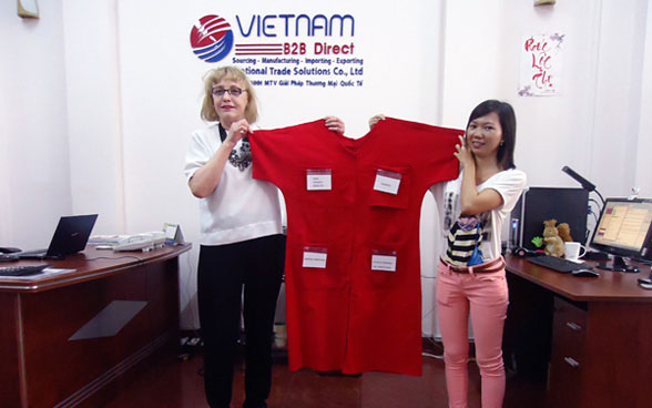 Entrepreneur Jeanne Mattick (USA) with Nhung Nguyen of Vietnam B2B Direct displaying the prototype of Ms. Mattick's innovative Institutional Hospital Gown, currently being sourced and developed in Vietnam.
